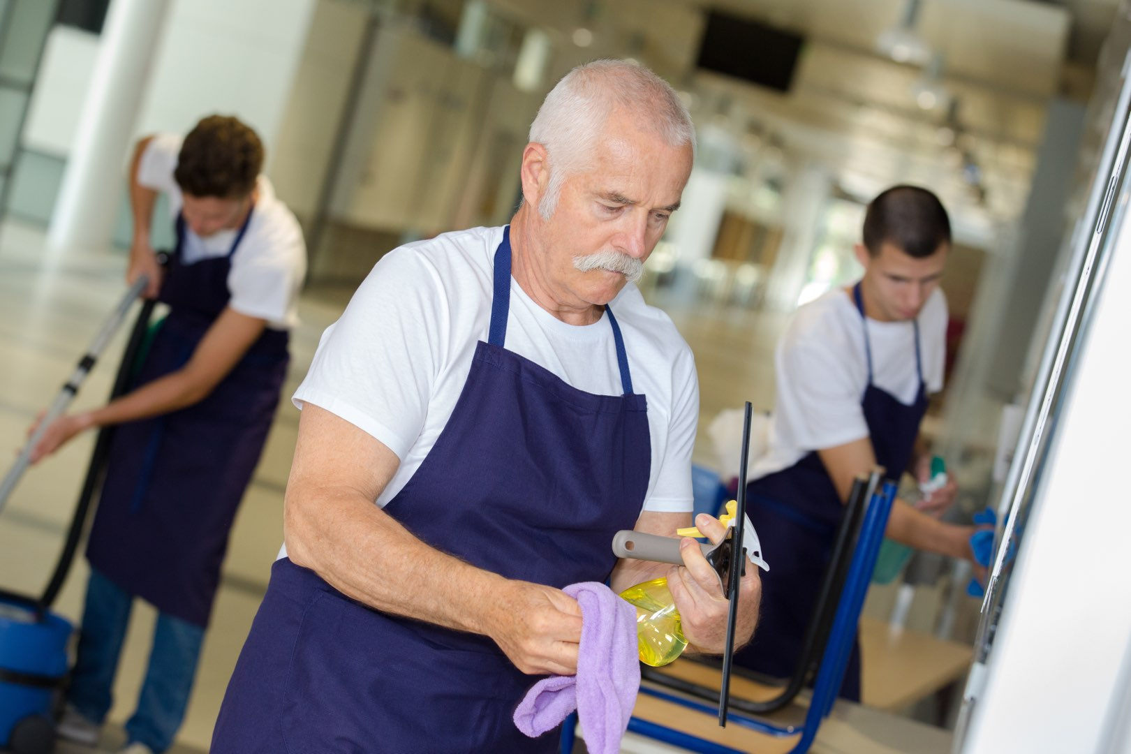 An older man holding a squeegee. commercial janitorial services