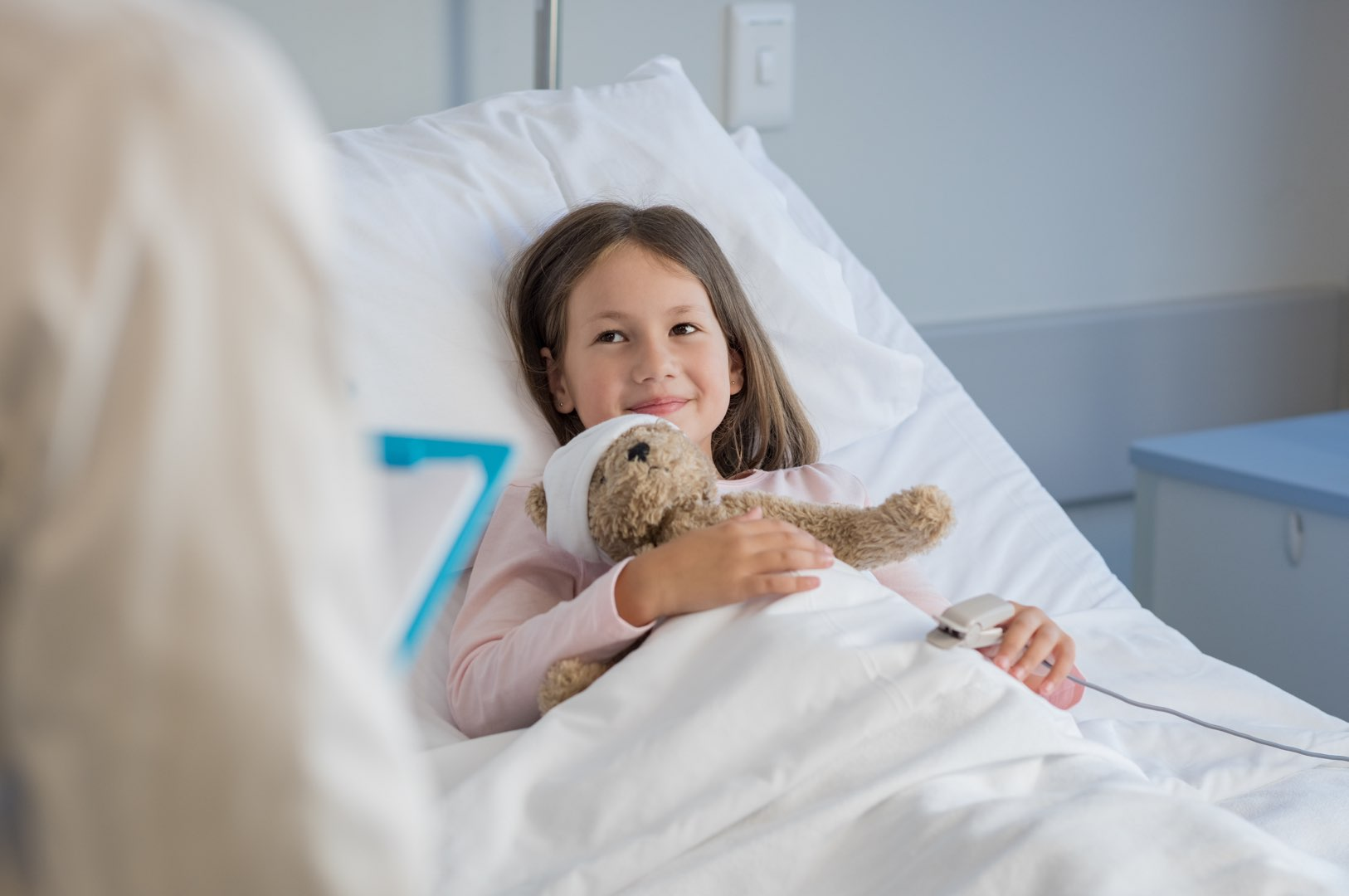 A little girl recovers in a hospital bed while holding her teddy bear, which had a bandage on its head.