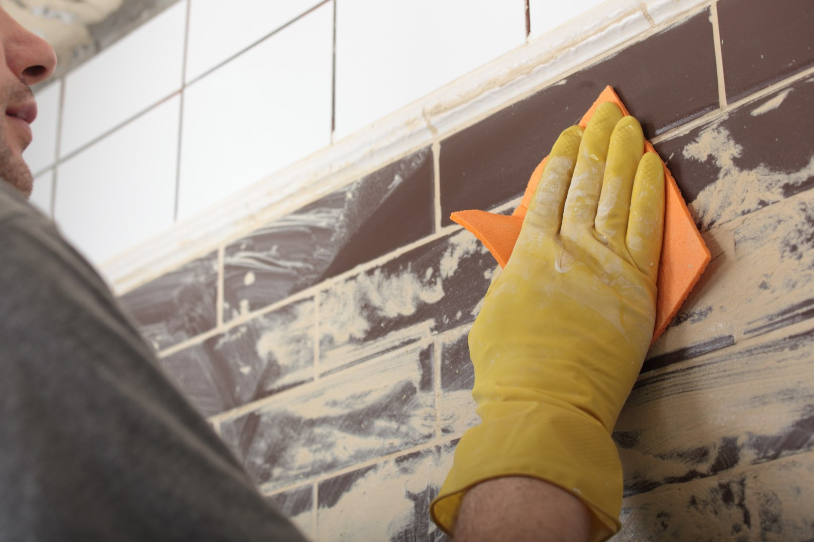 Grouting tile. Construction cleanup companies also use this practice as a final touch on tiled walls.