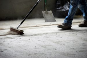 Sweeping up rough concrete flooring particles. Part of healthcare cleaning services is making sure all layers of flooring are spotless before final inspection.