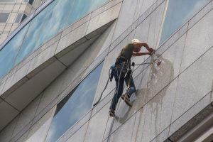 A window washer scales the outside of a building. Progressive Building Services also includes window cleaning.