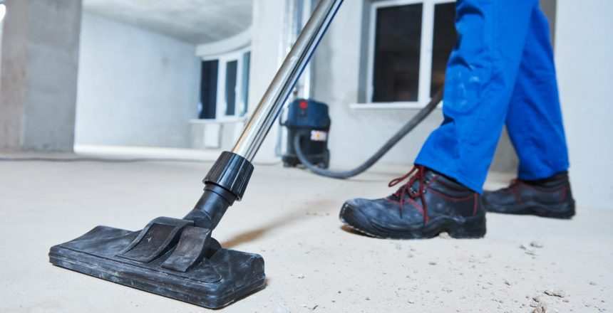 A uniformed man uses a heavy duty vacuum to complete construction cleanup.