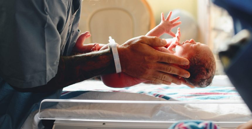 A father holds his newborn in the hospital. Reducing healthcare associated infections helps our most vulnerable.